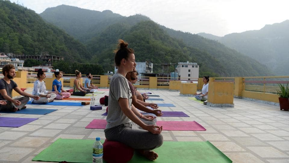 People practice yoga on a terrace at the Anand Prakash yoga ashram in Rishikesh, Uttarakhand. The town, in the foothills of the Himalayas 250 kilometres north of Delhi, is the world centre of yoga, drawing tens of thousands of foreign tourists every year to its dozens of ashram retreats and yoga schools. (Sajjad Hussain / AFP)