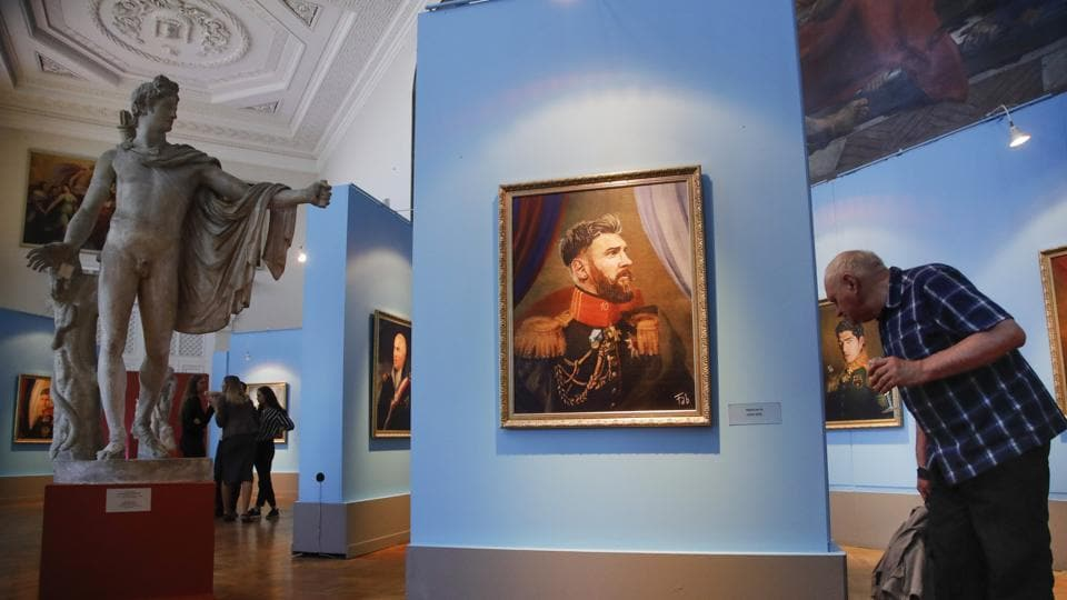 A visitor examines a portrait of Argentina footballer Lionel Messi at the Museum of Academy of Arts in St Petersburg. (AP)