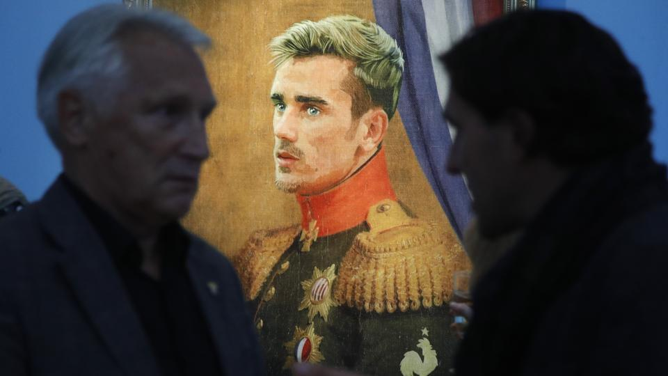 Visitors speak in front of portrait of France's football star Antoine Griezmann's portrait. (AP)