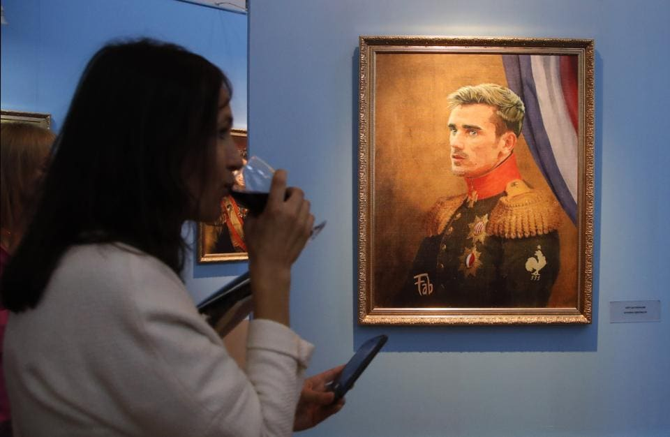 A visitor walks past portrait of France football team star Antoine Griezmann at the Museum of Academy of Arts. (AP)