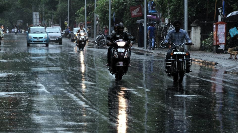 CALM BEFORE THE STROM: Commuters brave the rain on Tilak road on Sunday.   (HT PHOTO)