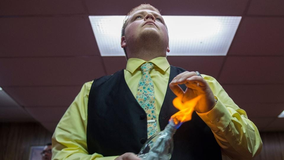 James Bass holds fire to his hand during a Pentecostal serpent handlers service at the House of the Lord Jesus church in Squire, West Virginia. Serpent-handling only plays a small part of the service, some of which last almost four hours. The rest of the time members proclaim their faith, dance; preach, and take communion. (Andrew Caballero-Reynolds / AFP)
