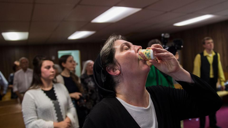 Robin Brandon drinks strychnine, a poison, as a test of faith during a service. Traditionally kept within the family, many members of the faith are related or closely connected. A few outsiders trickle in and some have become followers as well, but overall it feels like an extended family. (Andrew Caballero-Reynolds / AFP)