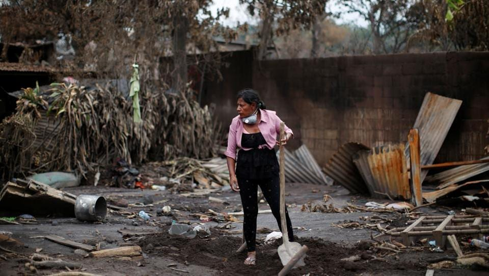 Eufemia Garcia Ixpata, a 48-year-old fruit vendor who lost dozens of family members during the eruption of the Fuego volcano, rests holding a shovel while searching for her family in San Miguel Los Lotes in Escuintla, Guatemala.  (Carlos Jasso / REUTERS)