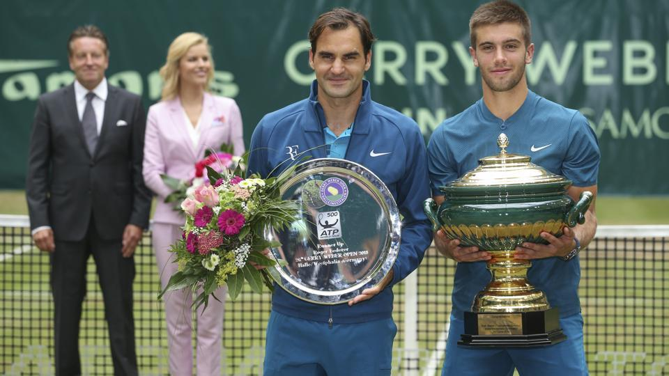 Croatia's Borna Coric (R) and Switzerland's Roger Federer (L) pose with the trophies during the winners ceremony at the Gerry Weber Open ATP tennis tournament in Halle, Germany, on Sunday.