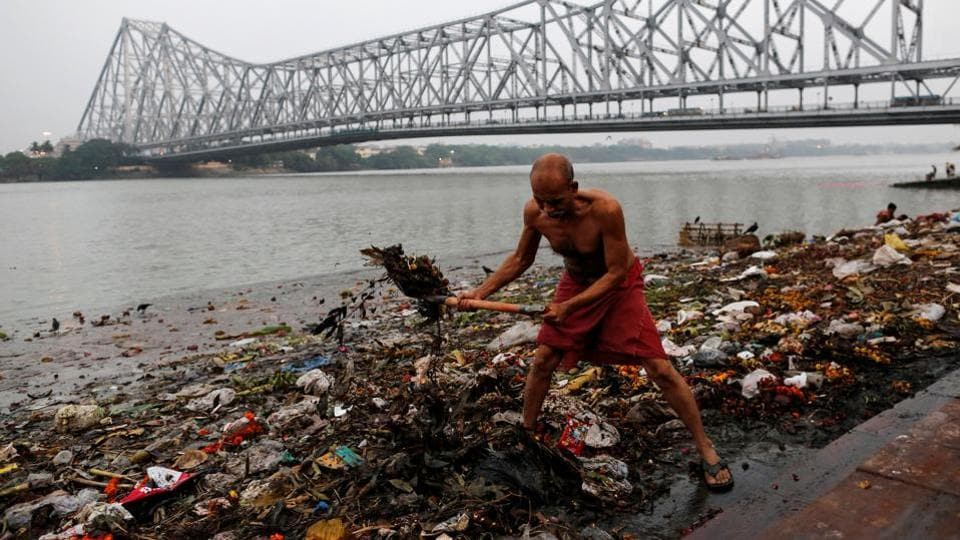 A man cleans garbage along the banks of the river Ganges in Kolkata, India, April 9, 2017.