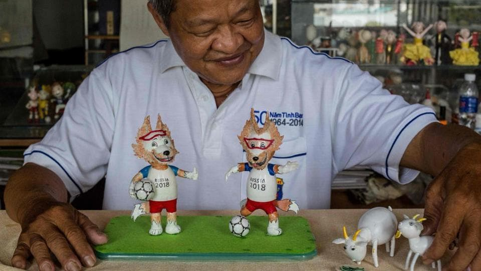 Retired Vietnamese English teacher Nguyen Thanh Tam displays two finished models of Zabivaka (L), the 2018 Russian World Cup mascot, made from eggshells, at his home in Ho Chi Minh City. Tam, 67, spends hours every day making the models, driven by his football fanaticism -- a passion shared by millions across Vietnam glued to the 2018 Football World Cup underway in Russia. (Thanh Nguyen / AFP)