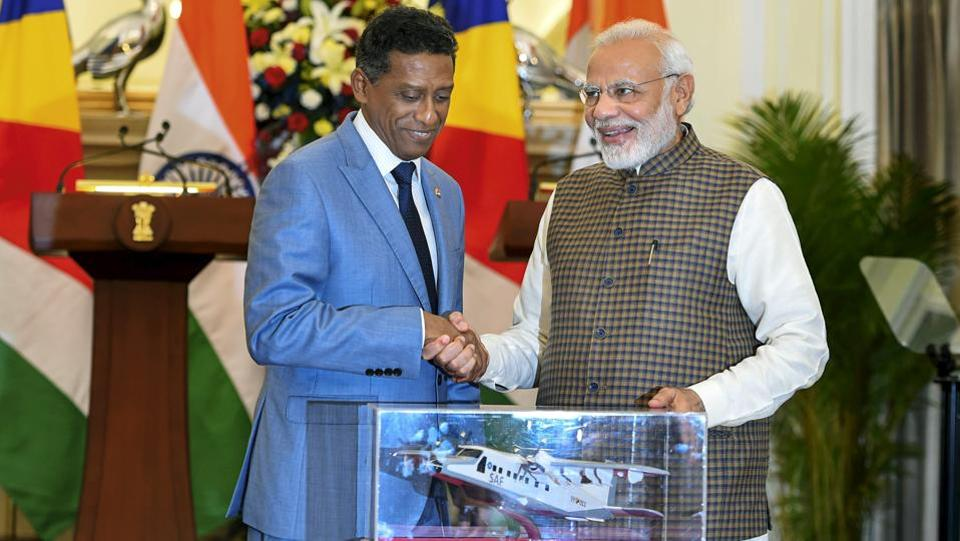 Prime Minister Narendra Modi poses with a model Dornier aircraft which will be gifted to Seychelles President Danny Antoine Rollen Faure, after their meeting at Hyderabad House, in New Delhi. India and Seychelles agreed to work together to develop a naval base at Assumption Island keeping mutual concerns in mind. India also announced a $100-million credit to Seychelles for augmenting its defence capabilities. (Shahbaz Khan / PTI)