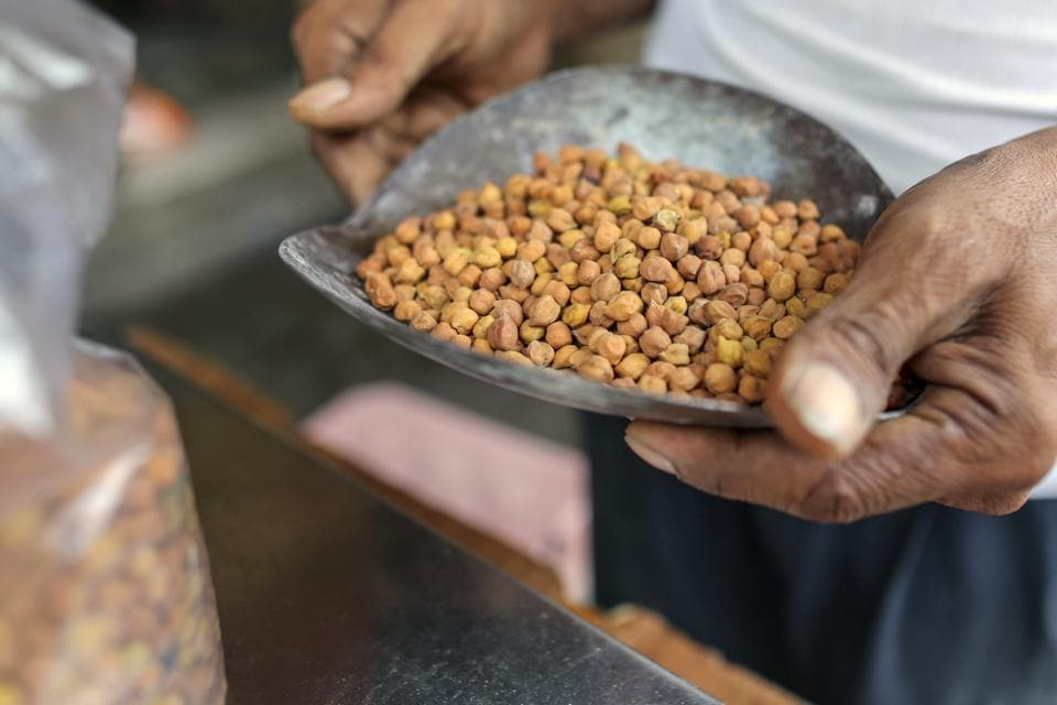 An employee holds a scoop of chickpeas in a store at a local market in Hyderabad, India.