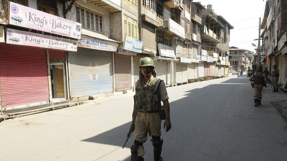 A paramilitary soldier stands guard in a closed market during a strike at Maisuma in Srinagar on Monday.