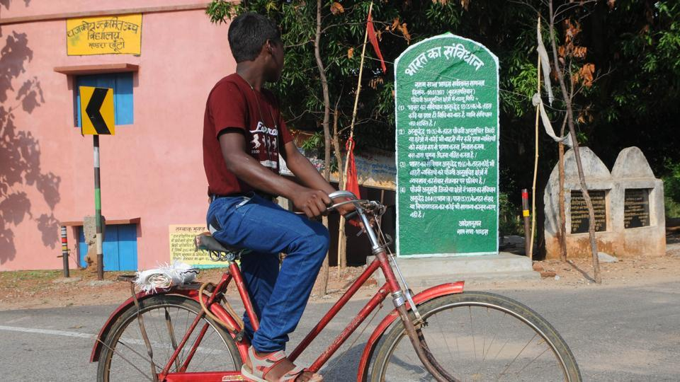 In this file pic, a passersby reads a plaque written in, Pathalgadi, a local dialectwhich carried certain articles of the Indian Constitution meant for 5th Schedule areas. It specifically warns outsiders from entering, wandering, living or settling down in tribal villages at Bhandra Village in Khunti District.