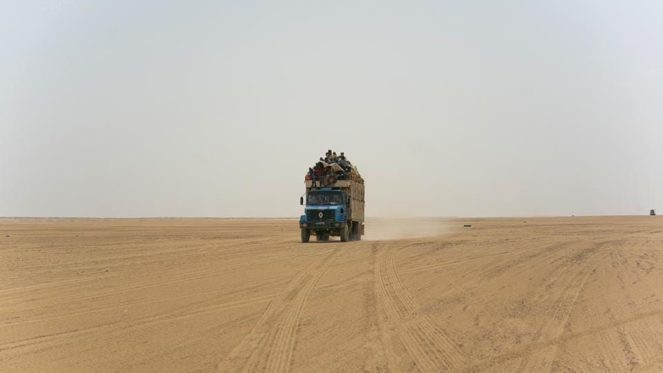 A truck carrying migrants drives through the Saharan Tenere in Niger. Once a well-worn roadway for tourists, the highway's 4,500 kms are a favoured path for migrants heading north. Here in the desert, Algeria has abandoned more than 13,000 people in the past 14 months, including pregnant women and children, stranding them without food or water and forcing them to walk, under temperatures of up to 48 degrees Celsius. (Jerome Delay / AP)