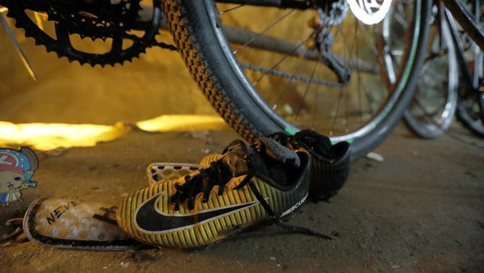 A pair of soccer shoes next to the abandoned bicycles belonging to the missing football team is seen at the entrance of a deep cave in northern Thailand while rescue personnel conduct operations under floodlights, seen in the background. Twelve children and their coach have been missing for four days since they entered the sprawling Tham Luang cave Saturday afternoon, after a morning intra squad match nearby. (Thai News Pix / AP)