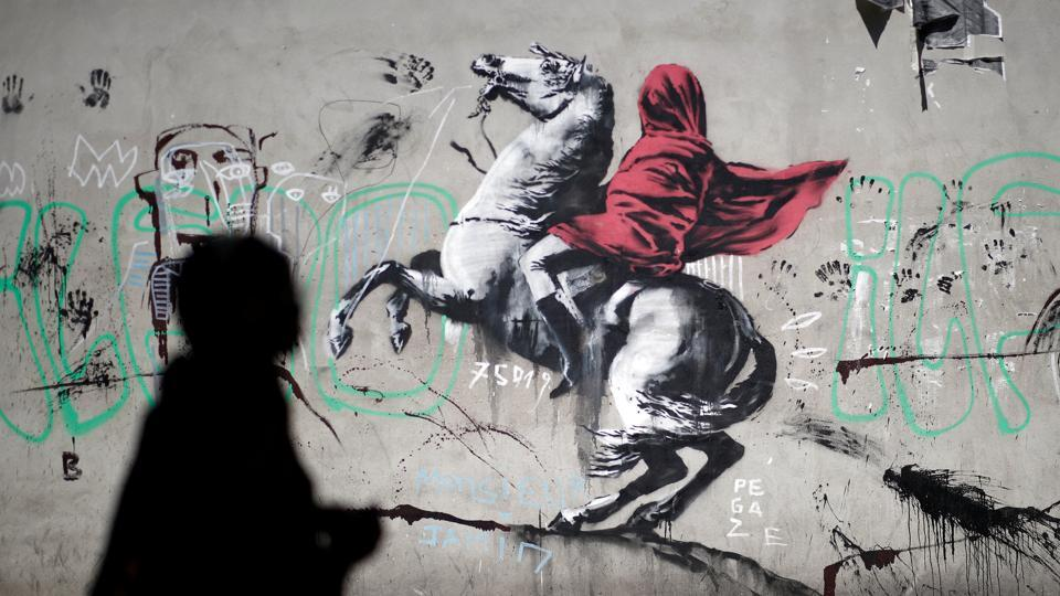 """Napoleon Crossing the Alps"", by French painter Jacques-Louis David with the red cloak, wrapped tightly around his face, an apparent reference to France's ban on face coverings in public places. The piece is among seven attributed to British activist-artist Banksy that have emerged since last week in Paris as governments row over how to treat people fleeing to Europe. (Benoit Tessier / REUTERS)"