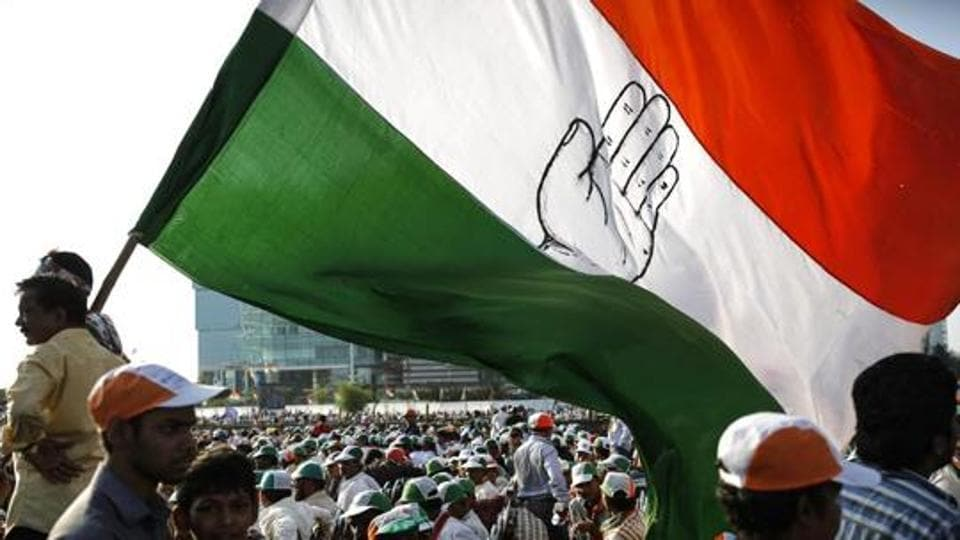 File photo of a Congress supporter holding a huge flag an election campaign rally in Mumbai.