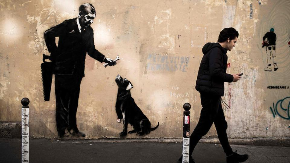 Other murals leave the viewer musing on greed or cruelty: In one a man in a suit is offering a one-legged dog a bone, while a handsaw behind his back raises the possibility that it is the dog's own leg. (Philippe Lopez / AFP)