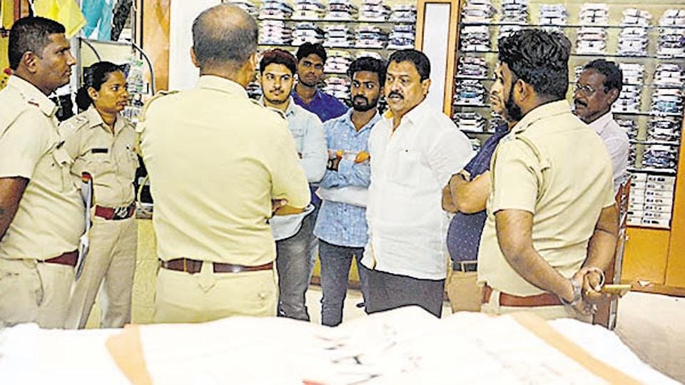 Arvind Shinde (centre) speaks to police personnel when the civic officials raided a garmet shop during the plastic ban.