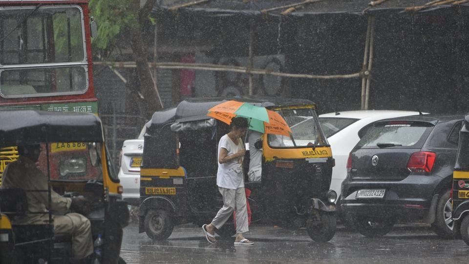 Commuters brave the rain at Versova, Mumbai on Tuesday. Karnataka also experienced another round of heavy rain after last week, leading to flooding of arterial roads and national highways in the cities and affecting vehicular movement in the state's coastal regions. (Satyabrata Tripathy / HT Photo)