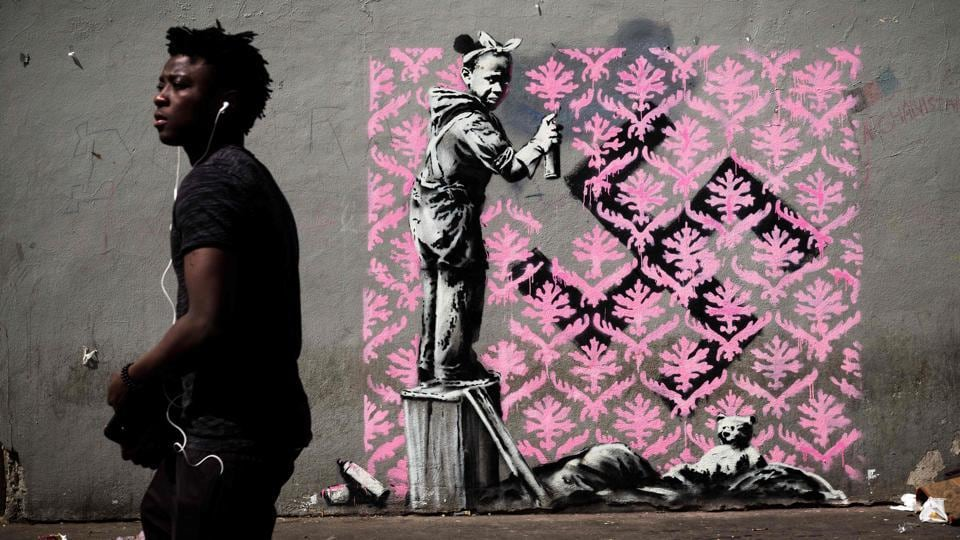 The works are believed to have started to appear as early as last Wednesday, UN-designated World Refugee Day, and some have already been vandalised. This mural, on a street in northern Paris where migrants sleep rough, shows a black girl spraying a pink wallpaper pattern over a swastika. (Philippe Lopez / AFP)