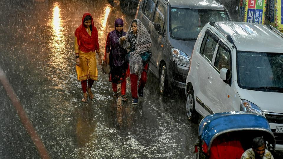 Pedestrians try to make their way across a street during heavy rain, in Lucknow on Tuesday. Forecasts of rain and thunderstorms at most places in the state on June 28 and June 29 are in place. The monsoon also advanced into most parts of Bihar yesterday, triggering light to moderate rainfall at a few places in the state. (Nand Kumar / PTI)