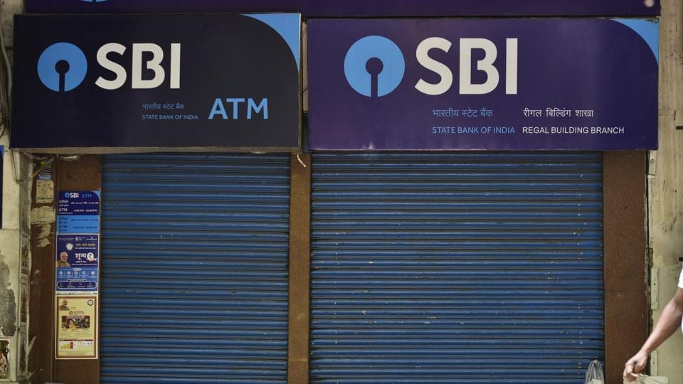 A man is seen sleeping on the pavement outside a branch of State Bank of India (SBI) at Connaught Place in New Delhi.