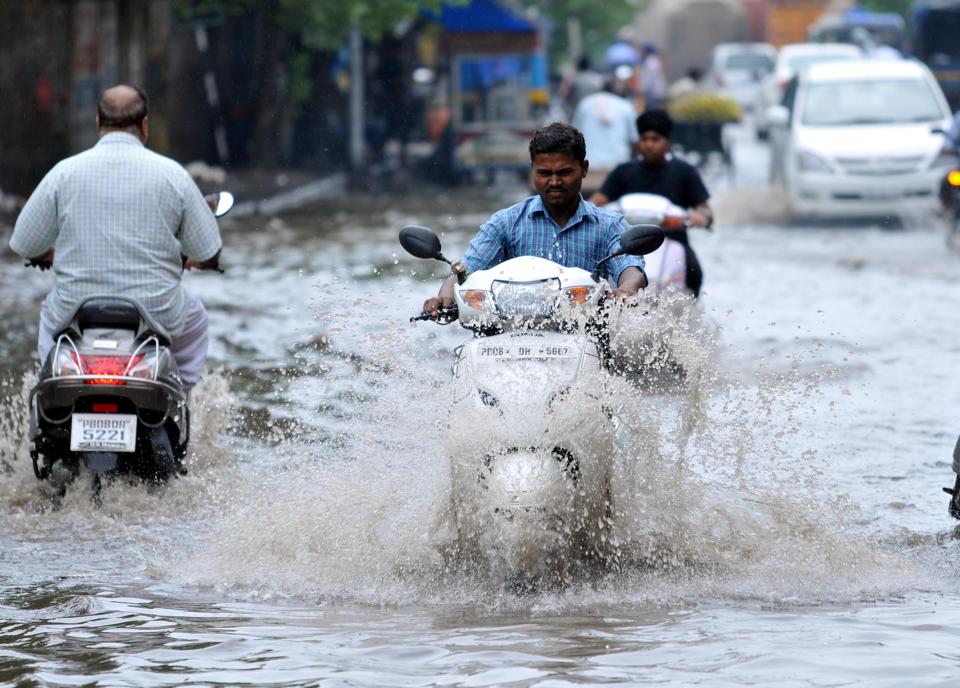 Vehicles wade through water-logged road after monsoon arrived in Jalandhar. (Pardeep Pandit/HT)