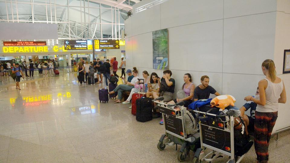 Passengers are seen waiting for flights outside the International Terminal at Ngurah Rai Airport after some flights were cancelled or rescheduled following an eruption of Mount Agung volcano in Bali, Indonesia.