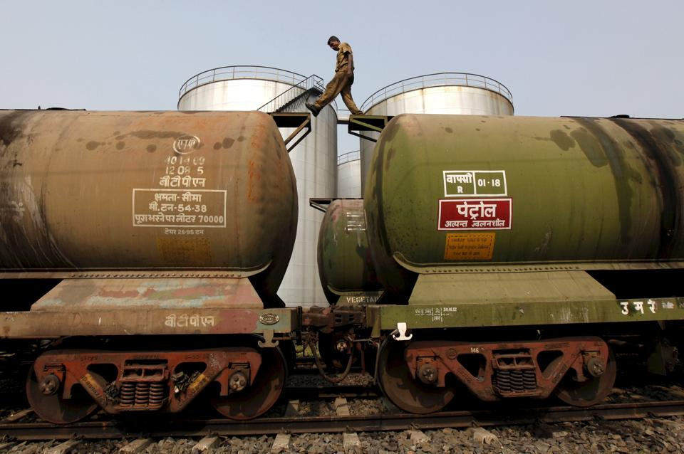 A worker walks atop a tanker wagon to check the freight level at an oil terminal on the outskirts of Kolkata, India.