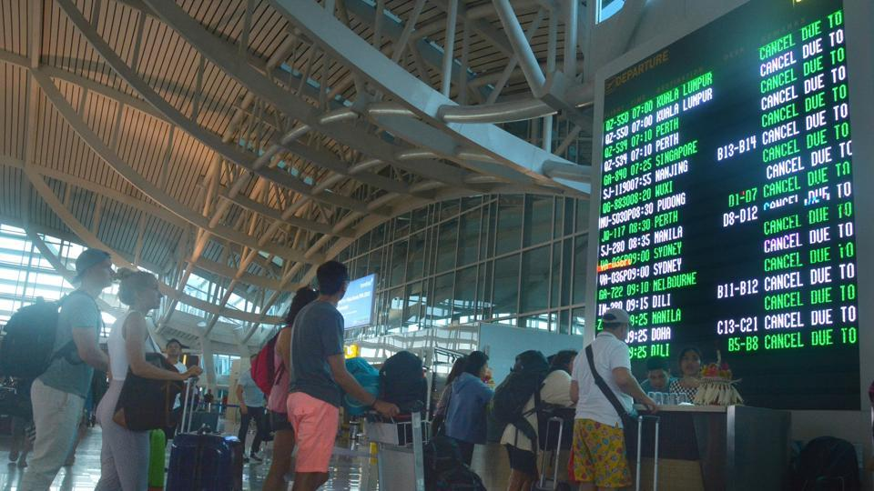 Passengers stand in front of a flight board as their flights are cancelled due to Mount Agung eruption at Ngurah Rai airport in Denpasar, Bali resort island, Indonesia, on Friday.