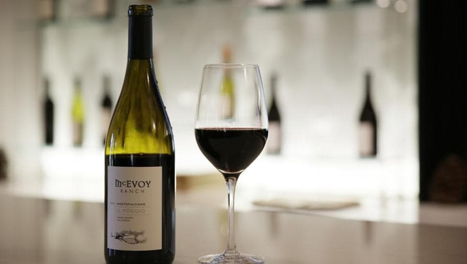 """A glass and bottle of McEvoy Ranch Il Poggio Montepulciano wine stand on a tasting room counter at the winery in Petaluma, California. The ranch is located in Northern California's Petaluma Gap which is one of America's newest viticultural areas and among the go-to places for wineries and vineyards hedging their bets against climate change. The area's slogan: """"From wind to wine."""" (Eric Risberg / AP)"""