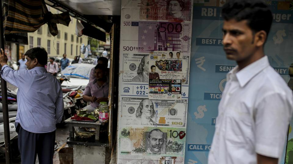 "A pedestrian walks past a currency exchange in Mumbai. ""Given India's current-account deficit, there is a need to fund it, but we are on track for a fifth consecutive month of bond outflows and the equity market has also been experiencing outflows,"" said Khoon Goh, head of Asia research at Australia & New Zealand Banking Group Ltd. in Singapore. Without a turnaround, the rupee may weaken past 70 per dollar, he said. (Dhiraj Singh / Bloomberg)"