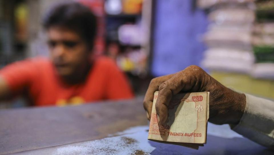 A man holds twenty rupee banknotes at a shop in Mumbai. The Indian rupee slumped to an all-time low as a resurgence in crude prices and the emerging-market sell-off took a toll on the currency of the world's third-biggest oil consumer. (Dhiraj Singh / Bloomberg)
