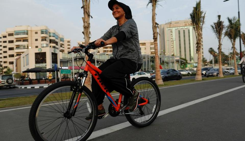Eman Joharjy, a fashion designer in one of her own creations, cycles along Jeddah's Corniche.