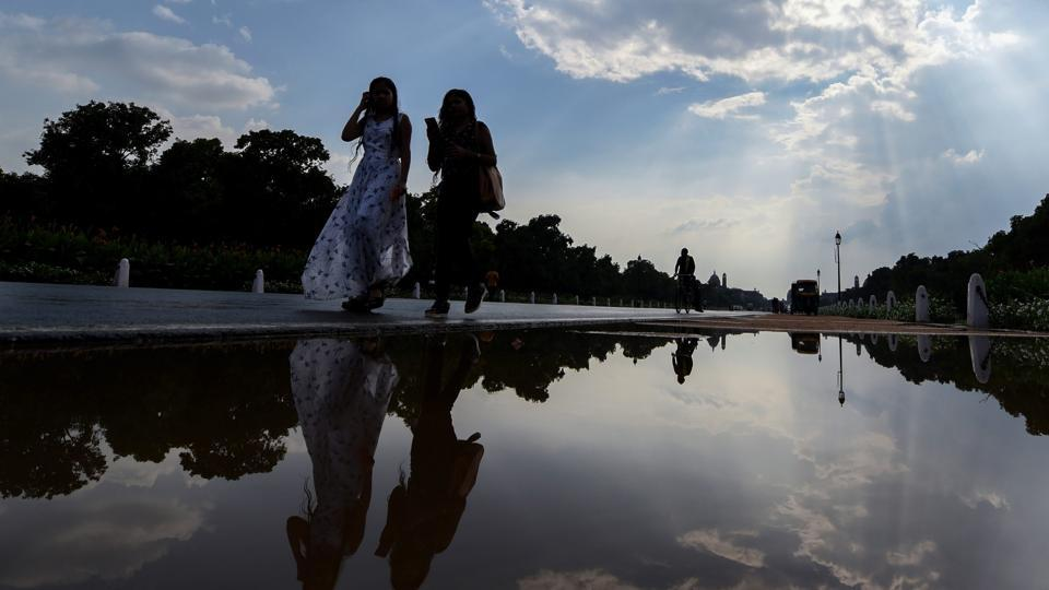 Women walk past a puddle of water at Rajpath after a short spell of rain in New Delhi on Thursday.