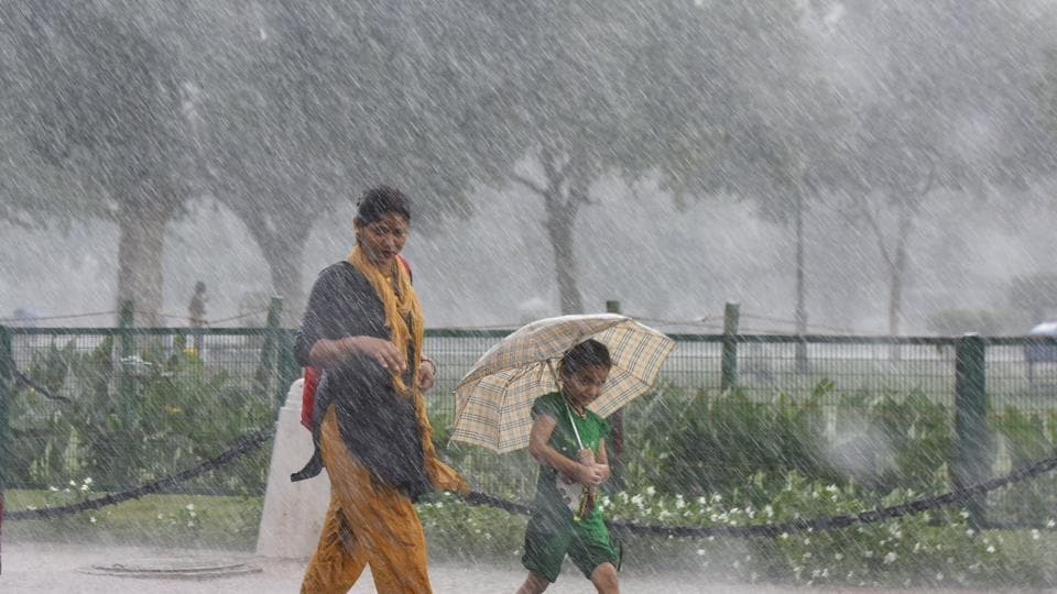 A girl walks under an umbrella with her mother during sudden rainfall, at Rajpath, in New Delhi, on Thursday.