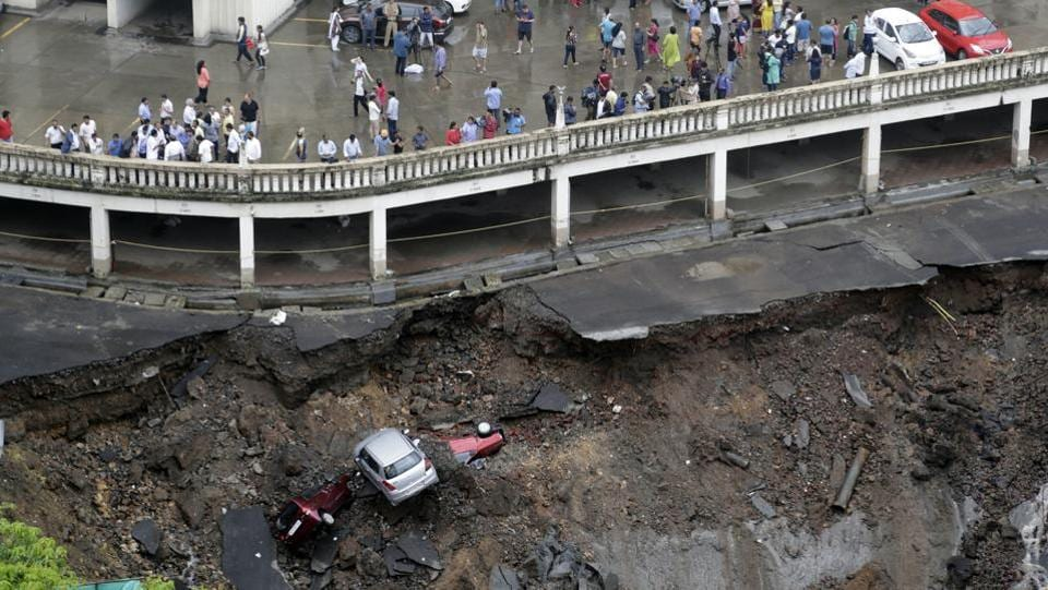 Cars lie buried in debris after the wall of an under construction building collapsed during heavy rains in Mumbai on June 25, 2018. (Rajanish Kakade / AP)