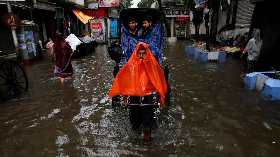 A rickshaw puller transports passengers through a water-logged street after heavy rain in Kolkata on June 26, 2018. (Rupak De Chowdhuri  / REUTERS)