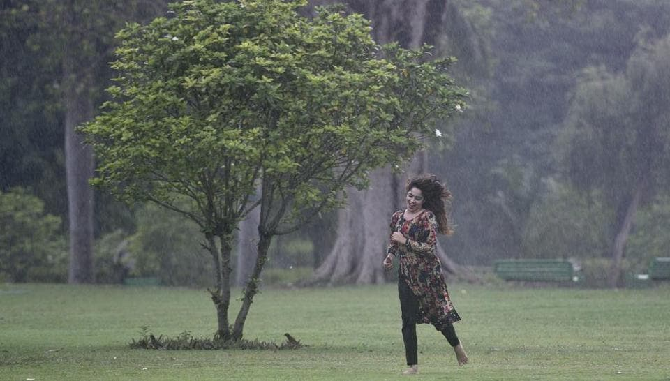 A girl enjoys in the rain at Lodhi Gardens in New Delhi, India, on Friday, June 29, 2018.