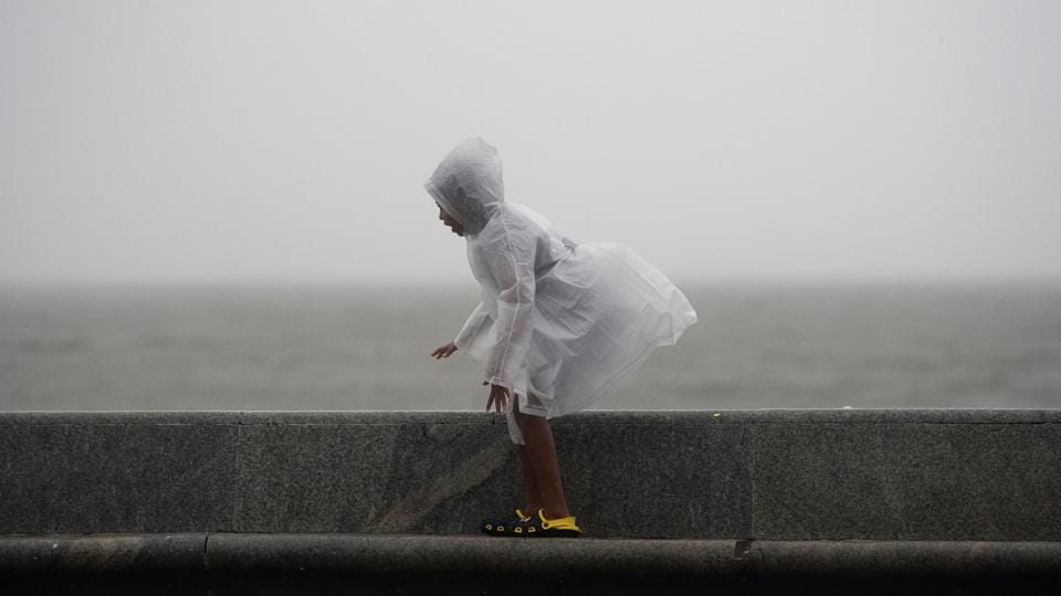 A child walks along the sea front during heavy monsoon showers in Mumbai on June 25, 2018. (Punit Paranjpe / AFP)