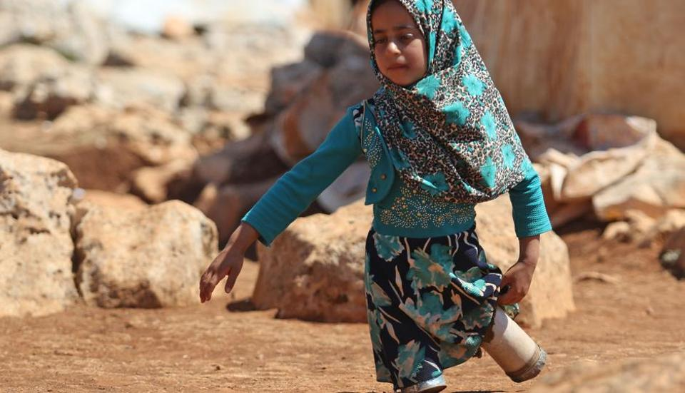 Eight year-old Maya Mohammad Ali Merhi walks using prosthetic legs made by her father from tin cans in a camp for displaced people, in the northern Syrian province of Idlib on June 20, 2018.