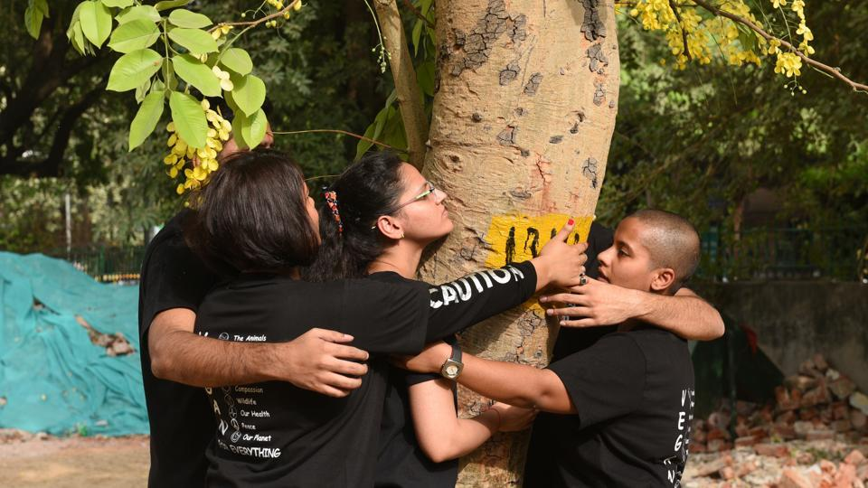 People hug a tree as they protest against the felling of trees at Sarojini Nagar in New Delhi on June 24, 2018. (Sonu Mehta / HT Photo)