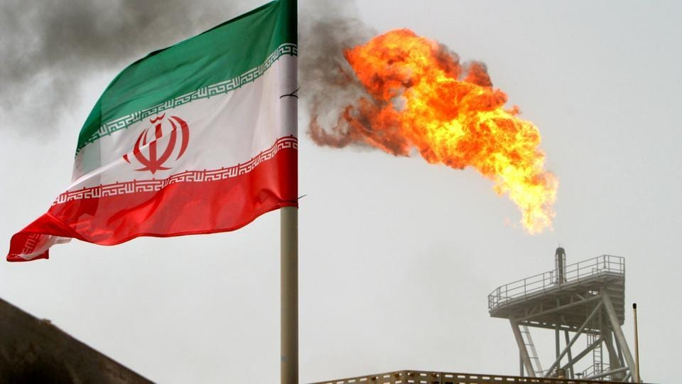 A gas flare on an oil production platform in the Soroush oil fields is seen alongside an Iranian flag in the Persian Gulf, Iran, July 25, 2005.