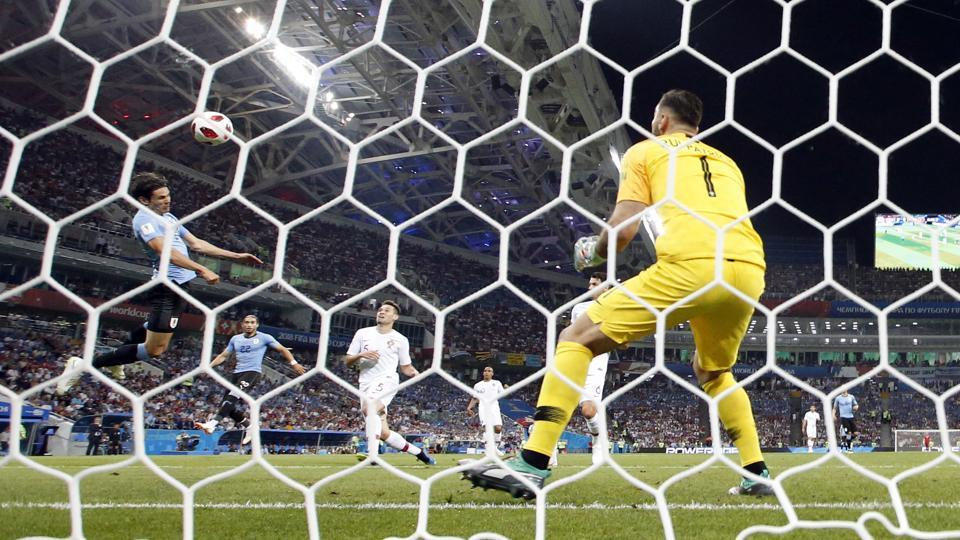 Uruguay's Edinson Cavani, left, scores his side's opening goal during the round of 16 match between Uruguay and Portugal at the 2018 soccer World Cup at the Fisht Stadium in Sochi. (AP)