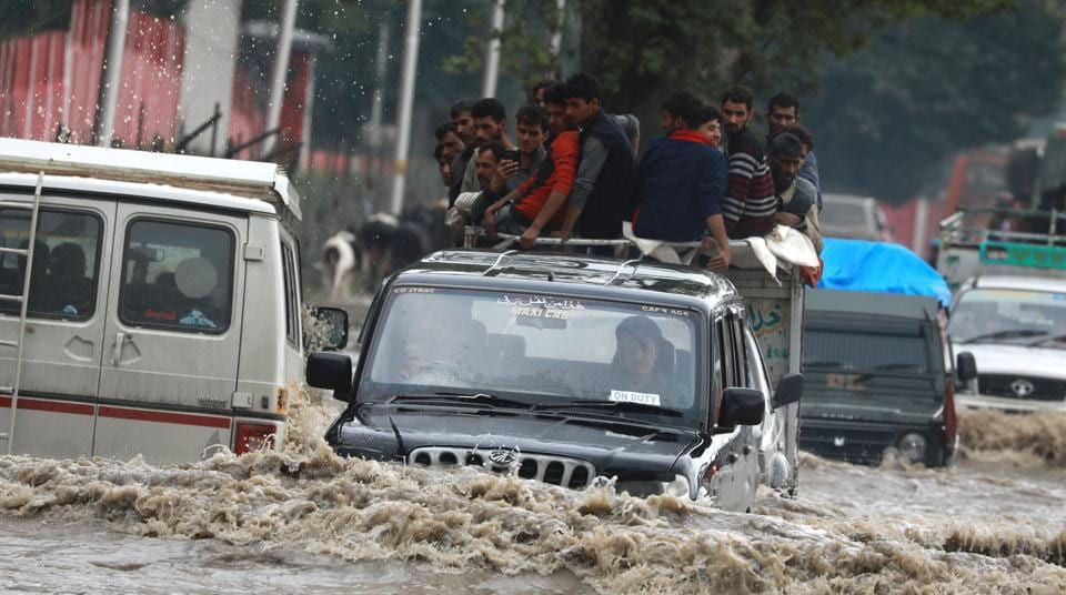 Vehicles wade through a flooded road after heavy rainfall in Srinagar on June 30.