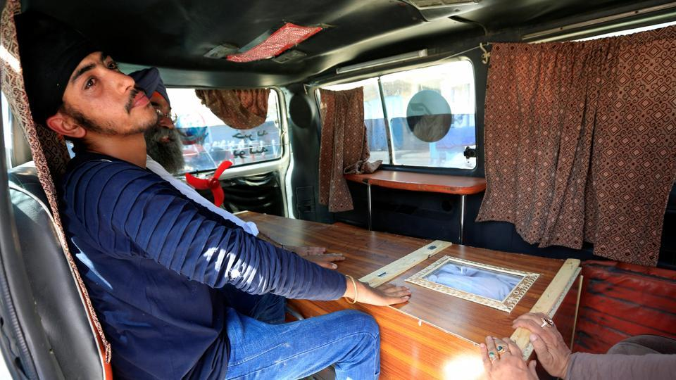 Afghan Sikh men sit next to the coffin of one of the victims of Sunday's blast in Jalalabad city, Afghanistan, on July 2, 2018.