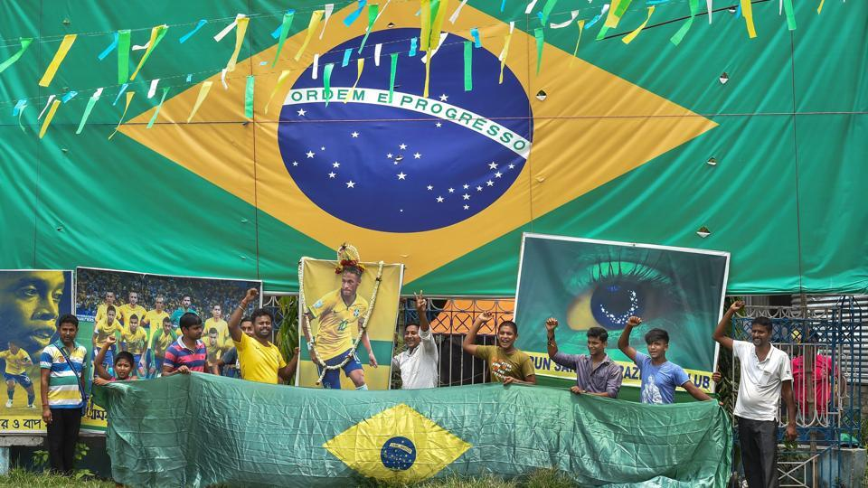 Supporters of the Brazilian football team in Kolkata, cheer against the background of a Brazilian flag ahead of the country's match against Mexico during FIFA World Cup 2018 on Monday. (Swapan Mahapatra / PTI)