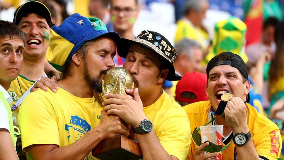 Brazil fans celebrate with a replica trophy during the match. (REUTERS)