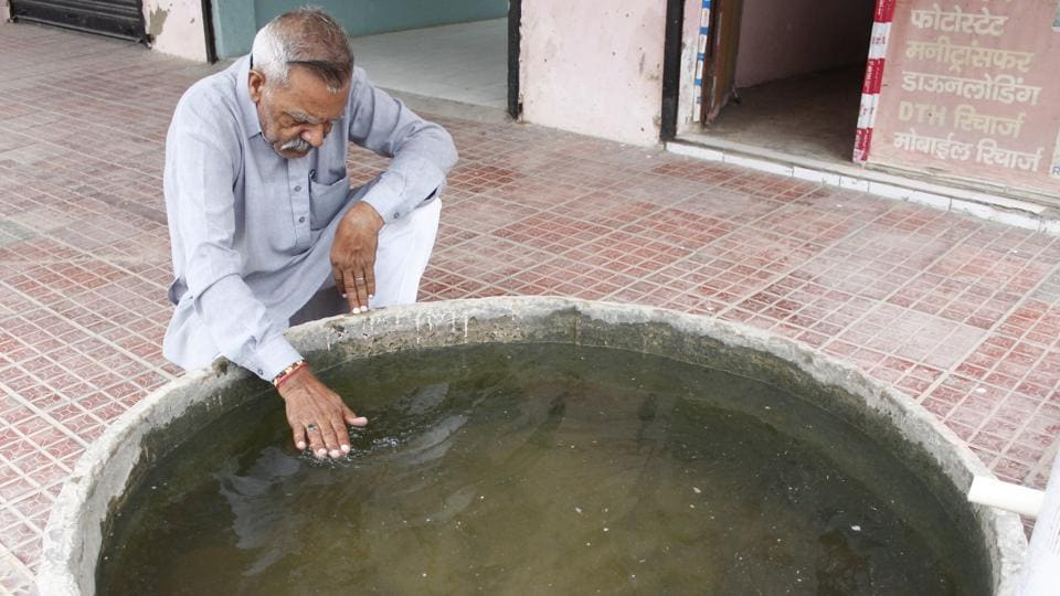 Karam Singh Tanwar whose wife died of cancer shows the poor quality of the village's borewell water. Tanwar ,who along with Chand carried out an informal survey to ascertain the nature and extent of cancer prevalence, said that he had managed to identify at least a dozen families in Bandwari who have lost a member to cancer over the last year and a half. (Yogendra Kumar / HT Photo)