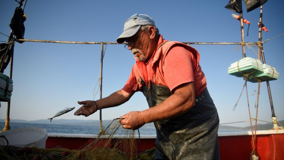 "Dimitris Karapetsas, 67, fishes onboard 'Katerina' off the shores of Asprovalta. ""I have been doing this job for 67 years. I have travelled to practically all of Greece, and now, I have reached my limitations,"" Pagonis said. ""I feel sad, I didn't want it to end this way."" (Alexandros Avramidis / REUTERS)"