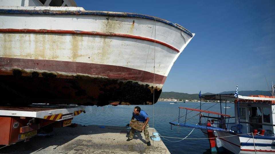 A worker kneels under 'Panagiotis' before it is sent for destruction. Payments range from 6,000 to 260,000 euros depending on the size of the boat. People can simply turn in their licences and find something else to do with their vessel. But to get the full payment, they have to take their boat to the scrap yard. (Alexandros Avramidis / REUTERS)